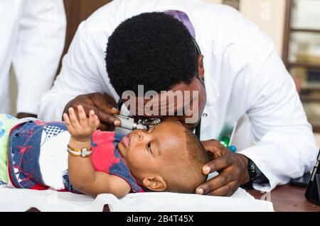 doctor in a white coat lurks in the baby's ear with a device in his office. - Stock Photo