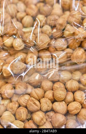 Packing from a transparent bag with peeled hazelnuts. Close up. Vertical.