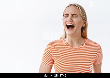 Miserable sad young whining blond girl acting immature, close eyes and shouting, crying heart out feeling unokay, standing uneasy suffering terrible - Stock Photo