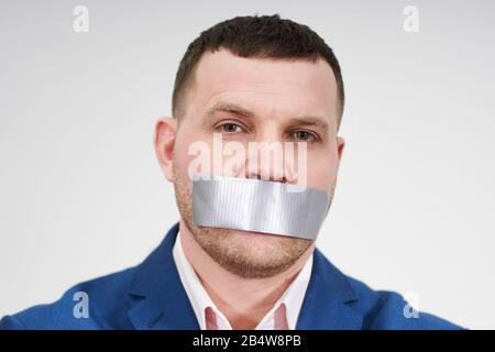man has a big piece of black industrial tape covering his mouth, silence concept - Stock Photo