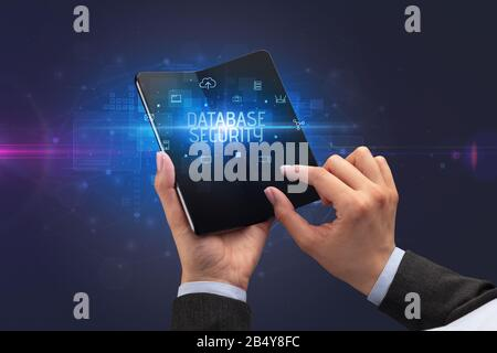 Businessman holding a foldable smartphone with DATABASE SECURITY inscription, cyber security concept