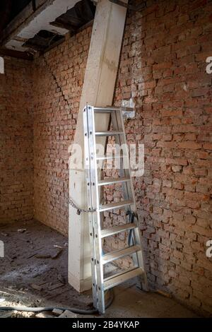 a ladder goes next to a wooden pipe covering on a building site - Stock Photo