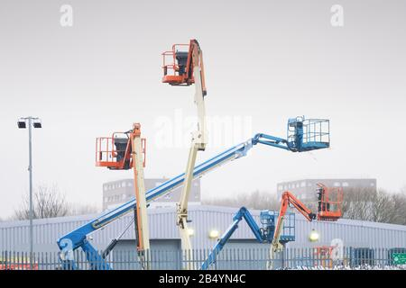 Access platform equipment powered high in sky in blue orange and yellow for high working platform height safety at construction building site - Stock Photo