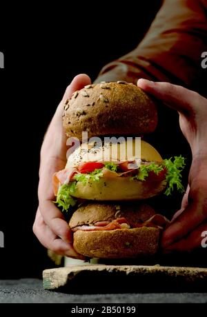 Young woman hands are holding delicious crispy burgers buns with sliced ham on a vintage wooden cutting board. Dark moody food still life. - Stock Photo