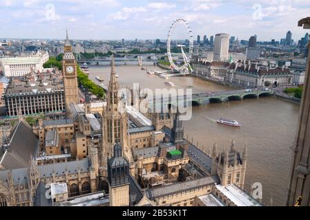 View looking over Palace of Westminster along River Thames towards the London Eye showing St Stephen's and Elizabeth towers. London, United Kingdom - Stock Photo