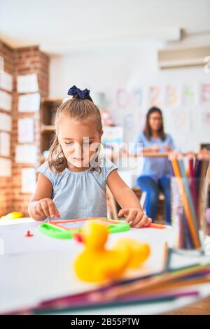 Caucasian girl kid playing and learning at playschool with female teacher. Mother and daughter at playroom around toys drawing on magnetic blackboard - Stock Photo