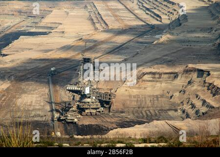 view into the brown cole opencast mine Hambach,  focus on a coal excavator that is working in the mine - Stock Photo