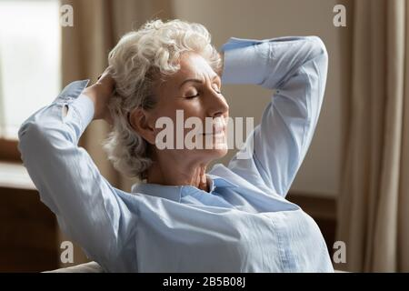 Calm senior woman relax on couch at home daydreaming - Stock Photo