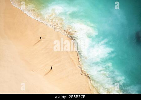 View from above, stunning aerial view of two people walking on a beautiful beach bathed by a turquoise sea during sunset. - Stock Photo