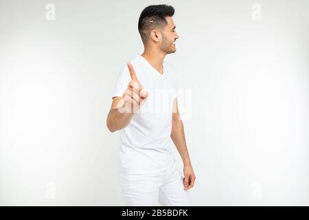 smiling man points his finger at the viewer and warns against a white studio background - Stock Photo