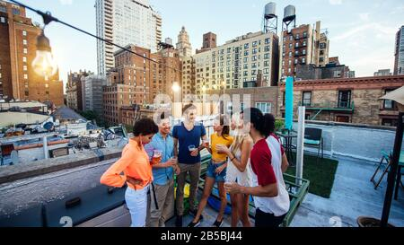 Group of friends spending time together on a rooftop in New york city, lifestyle concept with happy people - Stock Photo