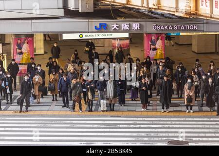 Osaka, Japan - March 4, 2020: Crowd of people wearing masks wait to cross street in front of JR Osaka Station - Stock Photo