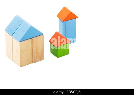 Houses made from children's wooden building blocks on a white background. - Stock Photo