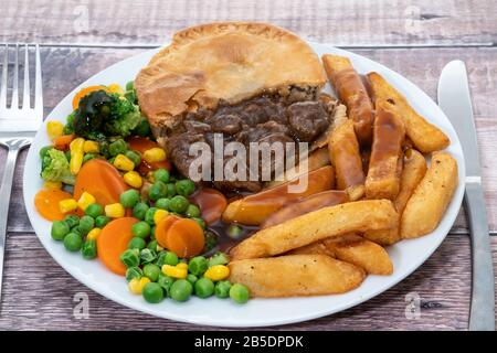 Beef steak pie, chips and vegetables - Stock Photo