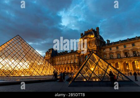 Evening view of the Louvre Museum with the pyramids lit and a dramatic sky in Paris, France.