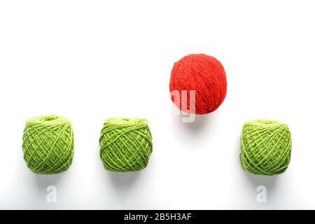 A unique red ball jumps out of a row of identical wool balls. Abstract concept of leadership, Be different. Teamwork in business and prerequisites for