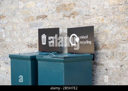 Close up of two rubbish bins, one with the sign for recycling and the other for general waste with a stone wall background. - Stock Photo