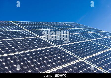Close-up, detail view of solar panels of a solar power plant in cloudless and bright blue sky