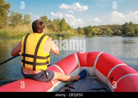 Rafting team , summer extreme water sport.  A man in a yellow life jacket with an oar floats in an inflatable boat on the river. Beautiful adrenaline - Stock Photo