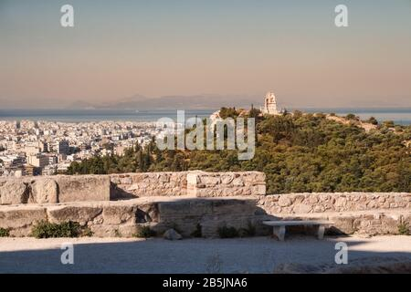 Athens cityscape. View from the Acropolis to city, Philopappus monument on hill and the Aegean Sea early morning at sunrise - Stock Photo