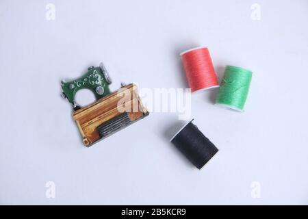Skeins of thread for needlework and sewing and sewing machine isolated on white background flat lay. Tailor still life set. Image contains copy space