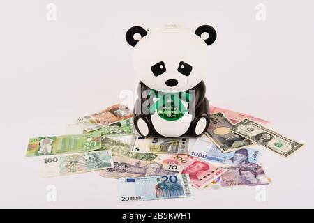 Panda bear piggy bank surrounded by different western and eastern world currencies