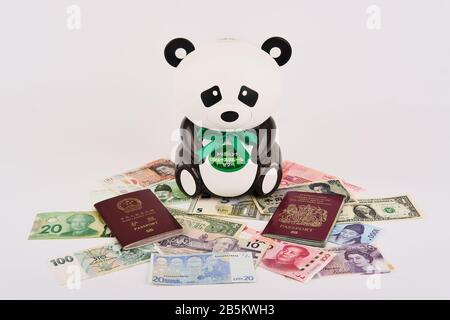 Panda bear piggy bank surrounded by different western and eastern world currencies and british and chinese passports