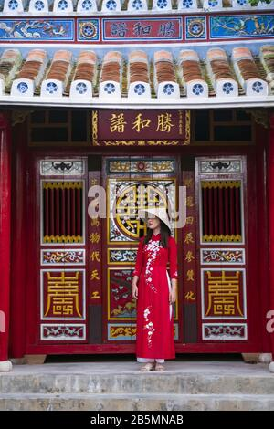A young Vietnamese woman wearing a traditional Ao Dai dress in the streets of old Hoi An - Stock Photo