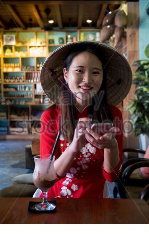A young Vietnamese woman wearing a traditional Ao Dai dress in the streets of Hoi An, Vietnam - Stock Photo