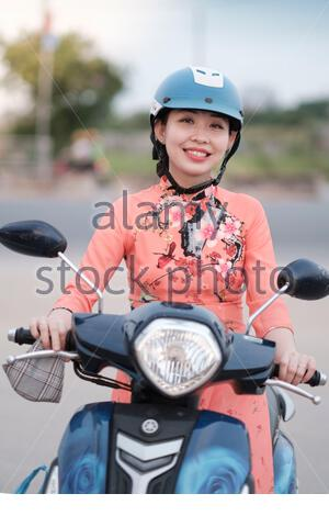 A young Vietnamese woman riding a motor scooter in Ho Chi Minh city - Stock Photo