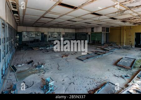 Broken electrical switchgear cabinets with control panels in abandoned factory. - Stock Photo
