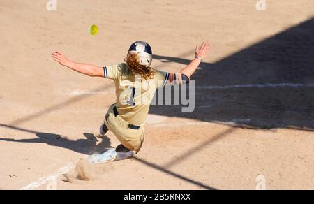 A Baseball Player is Sliding Into Home Base While the Ball is Flying Through the Air - Stock Photo