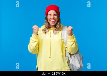 Happy cheerful blond girl in red beanie and yellow hoodie, close eyes relieved and smiling triumphing, celebrating great news, passed exams in - Stock Photo