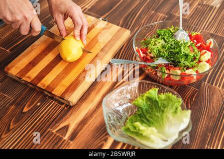 Young woman is cutting a lemon on cutting board for salad - Stock Photo