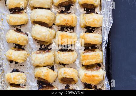 Baked sausage rolls on black table - Top view photo of puff pastry snacks in foil lined tin on black surface - ready to serve