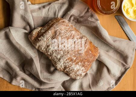 Whole loaf of rustic bread on cloth with butter and bread knife, top view photo - Stock Photo