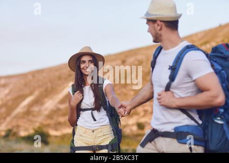 Hiking couple with backpack walking on hike in nature Stock Photo