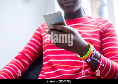 Close Up Of Teenage Girl Wearing Wristbands Using Mobile Phone At Home - Stock Photo