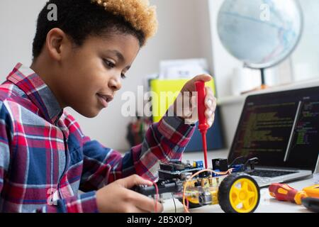 Male Elementary School Pupil Building Robot Car In Science Lesson - Stock Photo