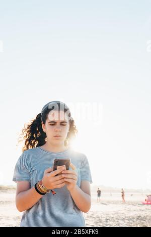 Pretty girl concentrates on reading on her mobile phone at the beach with back light and space for copy