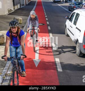 Cyclists using special cycling road on one-way-street - Stock Photo