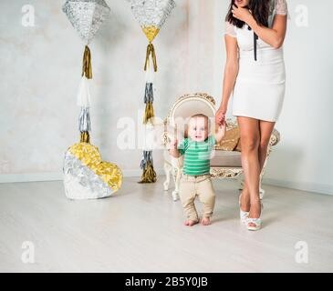 Slim unidentified young mother in a white dress and high heels walks by the hand with her smug, one-year-old barefoot son taking his first steps in a - Stock Photo