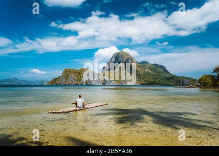Man meditating on bamboo float surrounded by shallow lagoon water and and Islands of Cadlao bay in a distance. Palawan, Philippines. Holiday vacation
