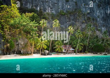 Secluded remote beach with hut under palm trees on Pinagbuyutan Island. Amazing lime stone rocks, sand beach, turquoise blue lagoon water.