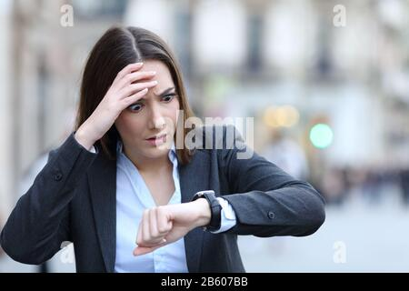 Front view of a worried business woman checking time on her smart watch on a city street - Stock Photo