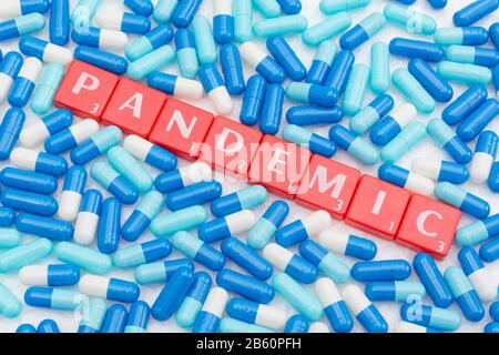 Drug capsules / pills & Letter tiles with word PANDEMIC. For 2020 Coronavirus pandemic, COVID-19, CV19, Wuhan virus, medication, SARS, MERS, new virus - Stock Photo