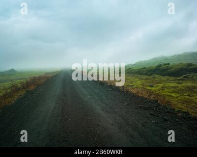Gravel road leading into a misty valley, rocky mossy green landscape volanic dirt track - Stock Photo