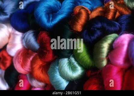 Brightly coloured balls of silk thread displayed on a market stall in Vientiane, Laos - Stock Photo