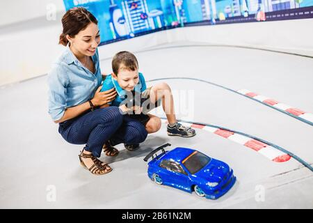 Little boy with his mother playing with radio remote controlled car at the training ground - Stock Photo