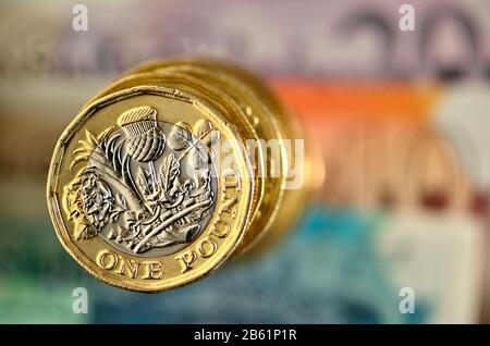 Pile of British pound coins on banknotes - Stock Photo